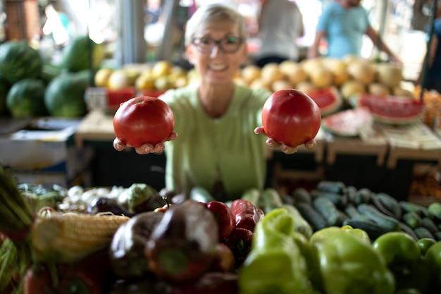 Oudere vrouw die verse biologische groenten koopt op de markt voor gezonde voeding. Premium Foto