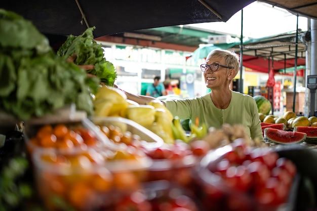 Oudere vrouw die verse biologische groenten koopt op de markt voor gezonde voeding.