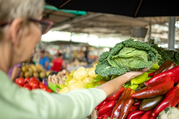 Oudere vrouw die verse groenten en fruit koopt op de markt en een zak vol gezond voedsel vasthoudt