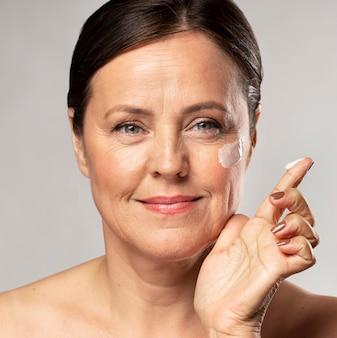 Oudere vrouw die vochtinbrengende crème op haar gezicht gebruikt