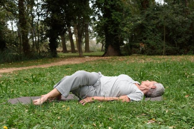 Oudere vrouw die yoga in het buitenland uitoefent