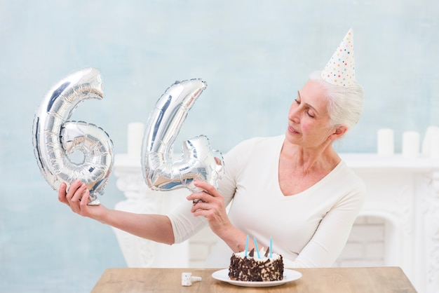 Oudere vrouw die zilveren folieballon op haar 64ste verjaardag bekijkt