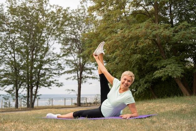 Oudere vrouw doet yoga buiten in het park
