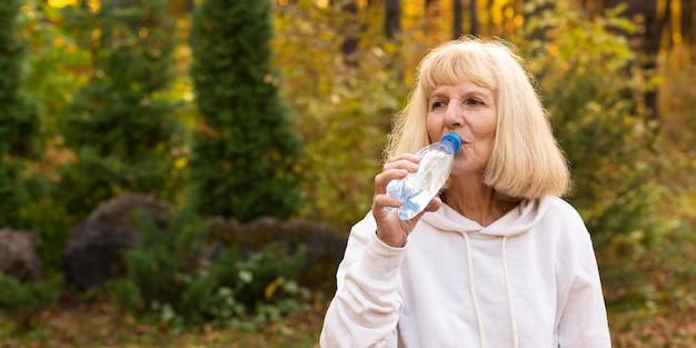 Oudere vrouw drinkwater buitenshuis