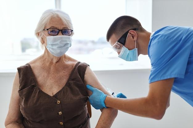 Oudere vrouw en dokter ziekenhuis vaccin paspoort behandeling immuniteit bescherming. hoge kwaliteit foto
