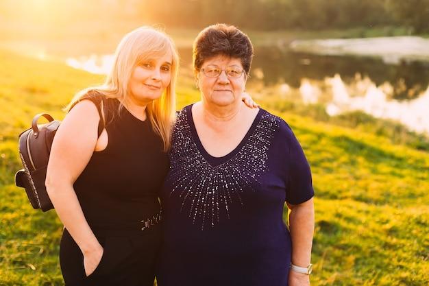Oudere vrouw en haar schoondochter omhelsden elkaar en kijken naar de camera