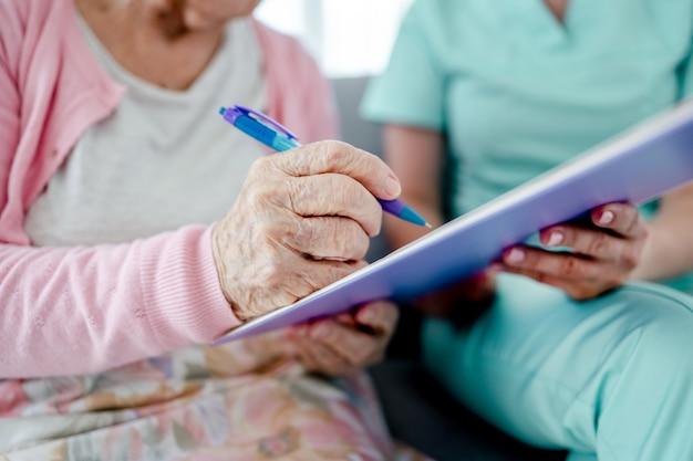 Oudere vrouw en verpleegster handen ondertekenen documenten thuis close-up. gezondheidszorg werknemer meisje en senior vrouwelijke persoon met papieren binnenshuis
