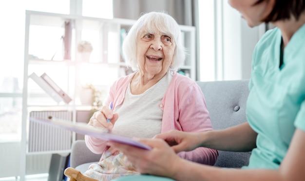 Oudere vrouw en verpleegster ondertekenen thuis medische documenten. gezondheidszorg werknemer meisje en senior vrouwelijke persoon binnenshuis