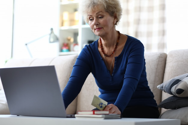 Oudere vrouw gebruikt een bankkaart om online te betalen.
