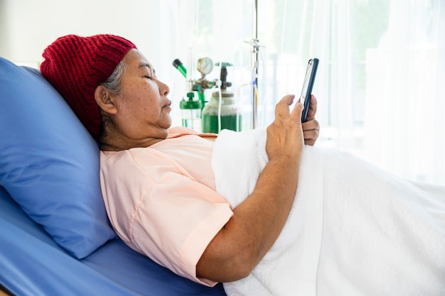 Oudere vrouw gebruikte smartphone op patiënt bed in het ziekenhuis