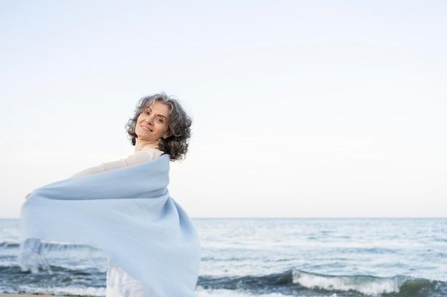 Oudere vrouw geniet van haar tijd op het strand