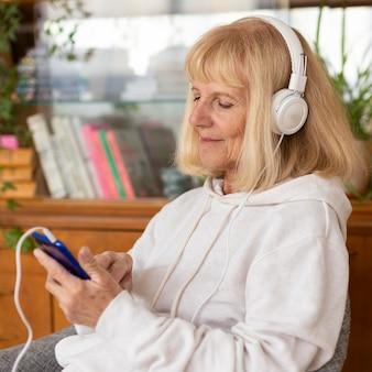 Oudere vrouw genieten van muziek thuis op koptelefoon