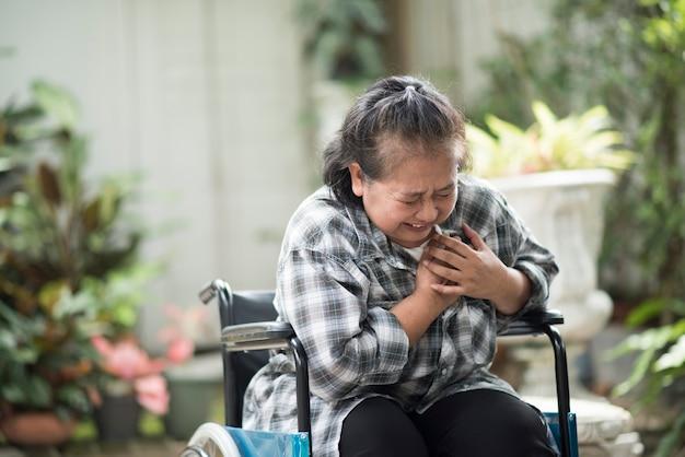 Oudere vrouw hebben een hartaandoening zittend op een rolstoel