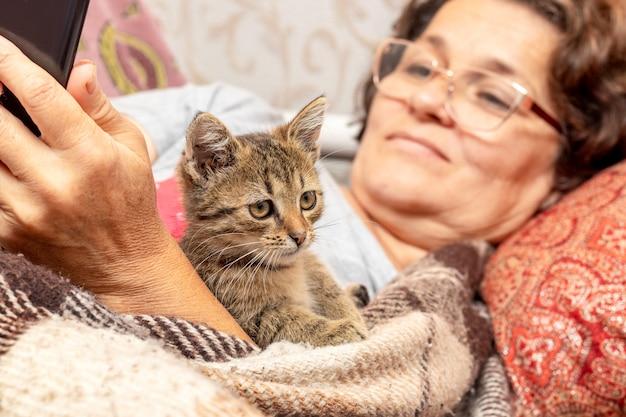 Oudere vrouw in bed met telefoon en kitten, liefde voor dieren
