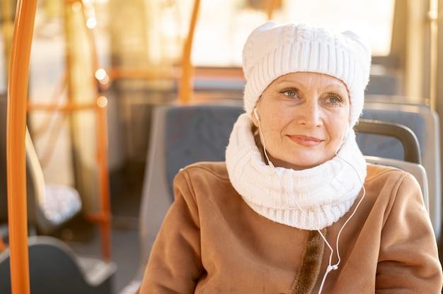 Oudere vrouw in bus het luisteren muziek
