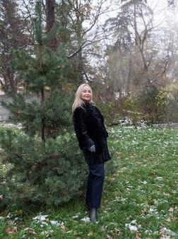 Oudere vrouw in een bontjas bij een kerstboom in het park