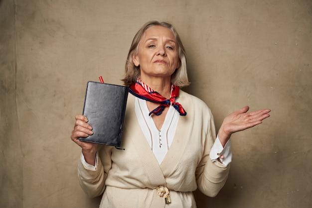 Oudere vrouw in een kamerjas met een notitieboekje in haar handen studiowerk