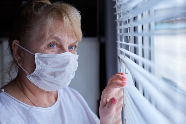 Oudere vrouw in een medisch masker in quarantaine en zelfisolatie