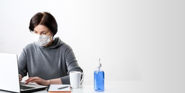Oudere vrouw in een medisch masker werkt op een computer. thuiswerken.