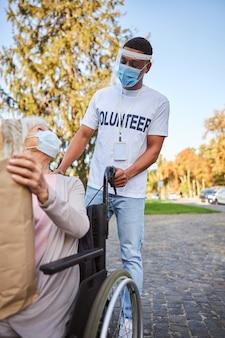 Oudere vrouw in een rolstoel met een medisch masker die zich tot een vrijwilliger in beschermend schild wendt en een boodschappentas vasthoudt