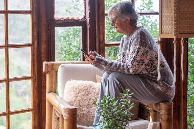 Oudere vrouw in een warme wintertrui ontspant thuis zittend op de armleuning met haar mobiele telefoon. comfortabele woonkamer, raam met uitzicht op het bos
