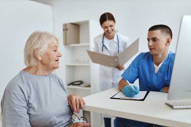 Oudere vrouw in het ziekenhuis bij de afspraak met de artsen en gezondheidsverpleegkundigen