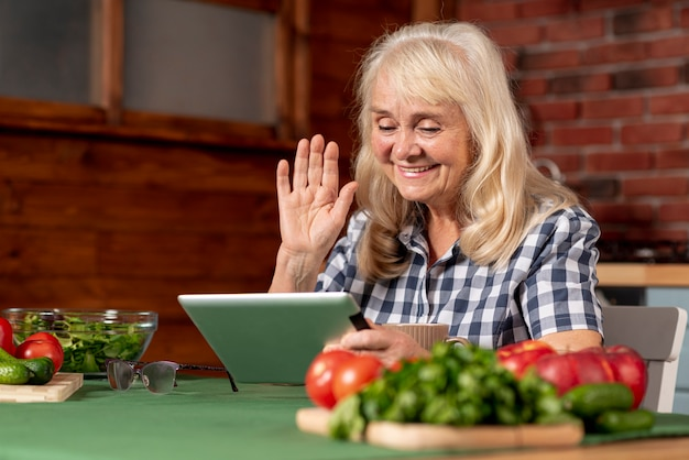 Oudere vrouw in keuken die tablet gebruikt