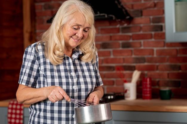 Oudere vrouw in keuken het koken