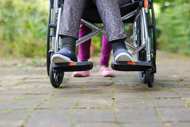 Oudere vrouw in rolstoel die met verzorger loopt