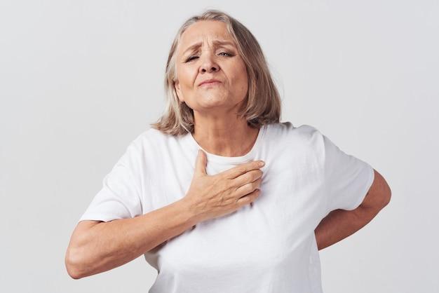 Oudere vrouw in witte tshirt gezondheidsproblemen behandeling ontevredenheid