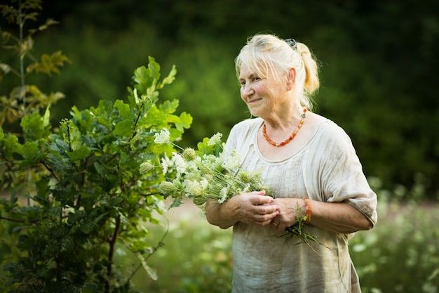 Oudere vrouw in witte vintage jurk loopt door de tuin met een boeket veldbloemen en glimlacht