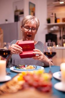 Oudere vrouw kijkt geschokt naar geschenkdoos tijdens feestelijk diner. gelukkig vrolijk bejaarde echtpaar dat samen thuis eet, geniet van de maaltijd, hun huwelijk viert, verrassingsvakantie