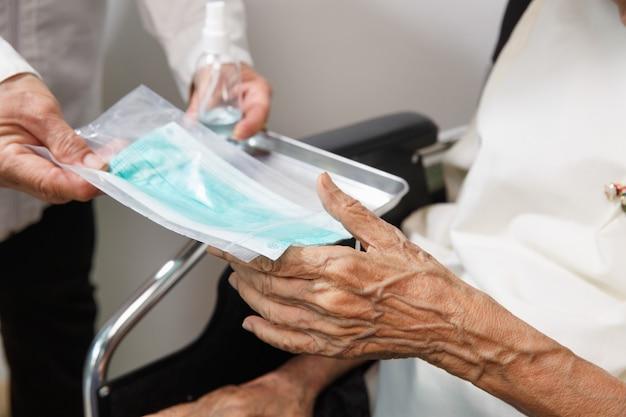 Oudere vrouw krijgt een masker van verzorger ter bescherming tegen coronavirus covid-19