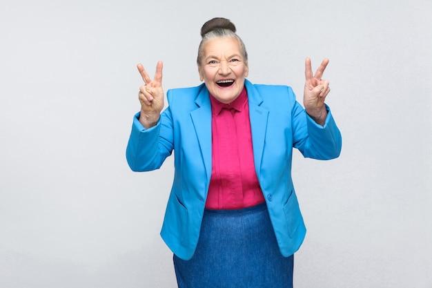 Oudere vrouw lacht en toont vrede of overwinningsteken op camera