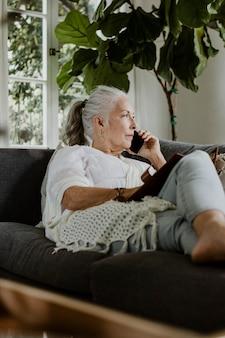 Oudere vrouw liggend en pratend op een telefoon op een bank