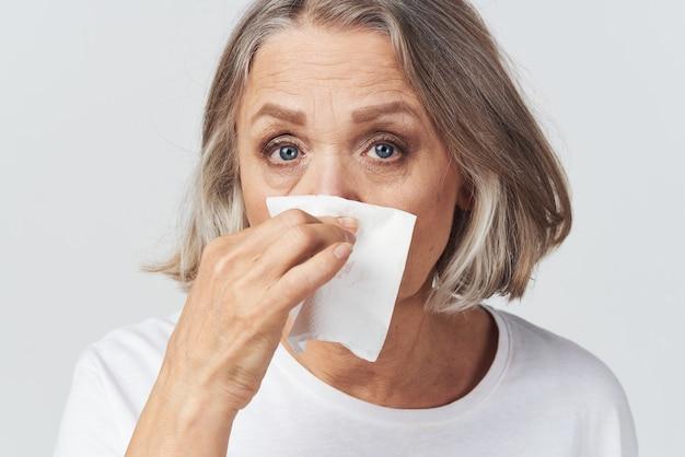 Oudere vrouw loopneus zakdoek koud