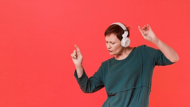 Oudere vrouw luisteren muziek en dansen