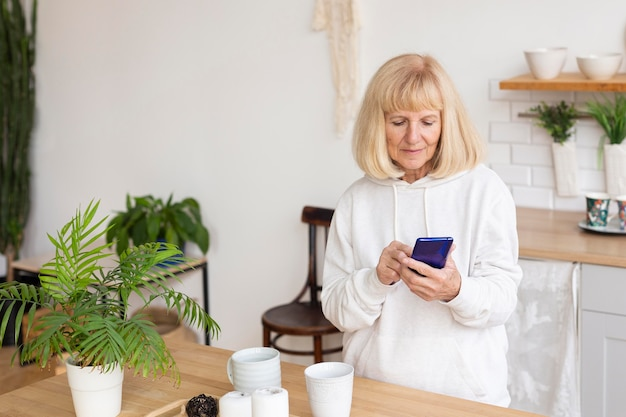 Oudere vrouw met behulp van smartphone thuis