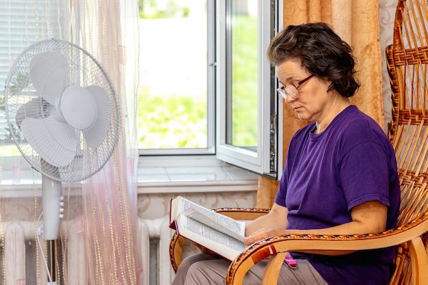Oudere vrouw met bril leest een boek bij het raam en een ventilator bij warm weer