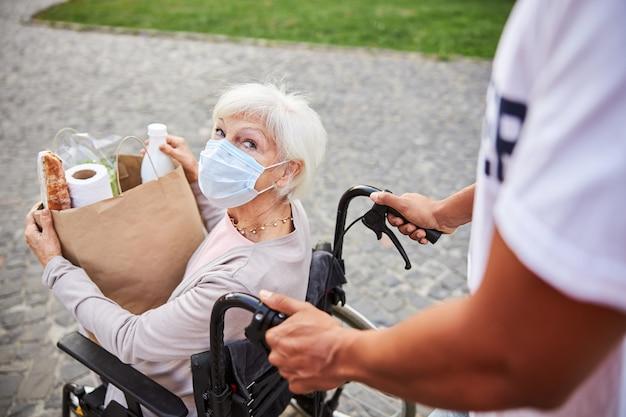 Oudere vrouw met een handicap die een medisch masker draagt en een papieren zak vol met aankopen maakt terwijl ze naar iemand kijkt die haar rolstoel voortduwt