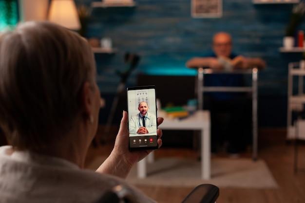 Oudere vrouw met een handicap die videogesprek gebruikt voor telegeneeskunde