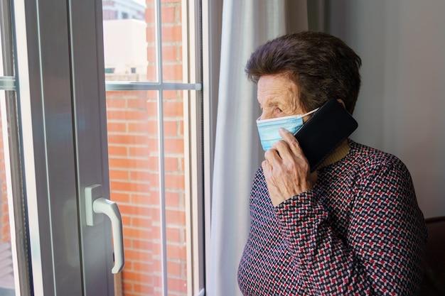 Oudere vrouw met een masker in haar huis kijkt uit het raam met angst voor de buitenkant, vanwege het coronavirus covid-19.