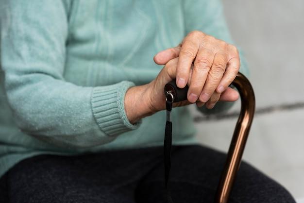 Oudere vrouw met een stok in haar handen