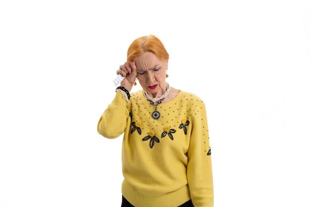 Oudere vrouw met geïsoleerde pillen dame heeft hoofdpijn tijd om aspirine te nemen