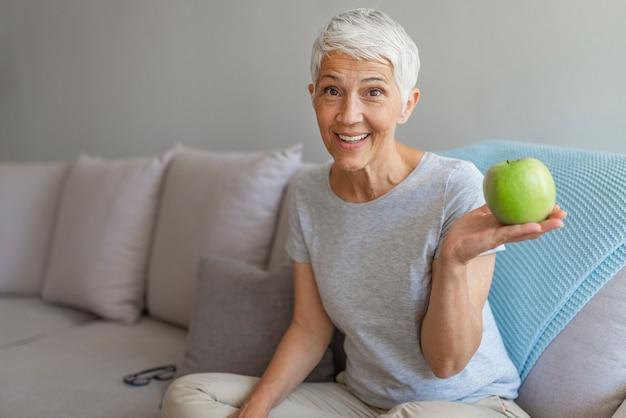 Oudere vrouw met gezond voedsel binnenshuis. gelukkige hogere vrouw met groene appel thuis.