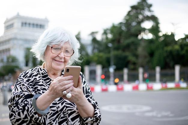 Oudere vrouw met haar mobiele telefoon op straat