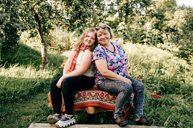 Oudere vrouw met jong meisje poseren op het platteland