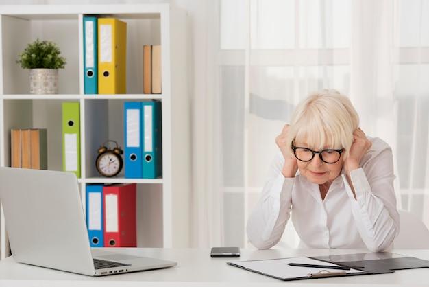 Oudere vrouw met klembord en laptop in haar kantoor