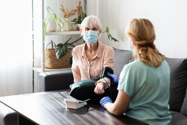 Oudere vrouw met medisch masker dat haar bloeddruk heeft gecontroleerd bij verpleeghuis
