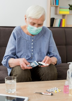 Oudere vrouw met medisch masker dat haar pillen neemt